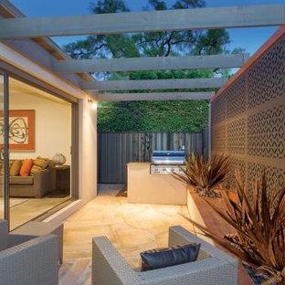 Immagine di un piccolo patio o portico eclettico in cortile con un giardino in vaso, pavimentazioni in pietra naturale e una pergola
