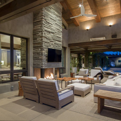 Patio - contemporary concrete patio idea in Phoenix with a roof extension and a fireplace