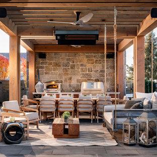 Ispirazione per un ampio patio o portico country dietro casa con pavimentazioni in cemento e una pergola