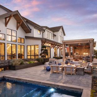 Immagine di un ampio patio o portico country dietro casa con un focolare, pavimentazioni in cemento e una pergola