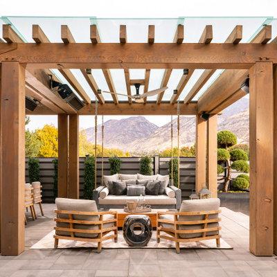 Example of a huge farmhouse backyard concrete paver patio kitchen design in Salt Lake City with a pergola