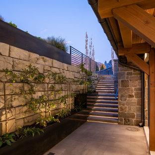 Foto di un grande patio o portico country in cortile con pavimentazioni in cemento e un tetto a sbalzo