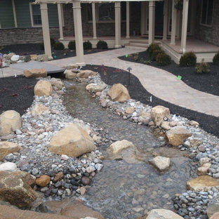Huge elegant side yard concrete paver patio fountain photo in Philadelphia with an awning