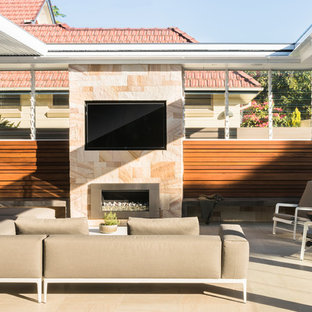 This is an example of a contemporary backyard patio in Sydney with with fireplace and a pergola.