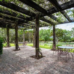 Esempio di un patio o portico country con pavimentazioni in mattoni e una pergola