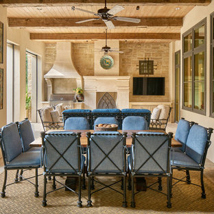 Photo of a large mediterranean back patio in Austin with an outdoor kitchen, tiled flooring and a roof extension.