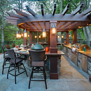 Photo of a transitional backyard patio in Minneapolis with an outdoor kitchen, natural stone pavers and a pergola.