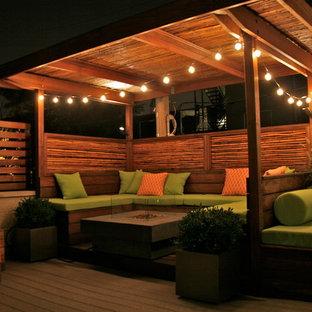 Ispirazione per un patio o portico eclettico di medie dimensioni con un focolare, pedane e un gazebo o capanno