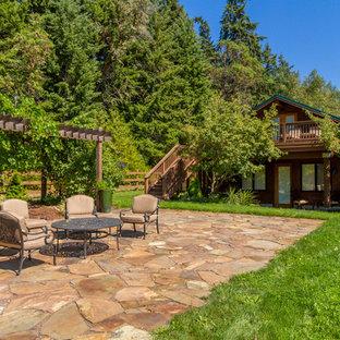 Idee per un ampio patio o portico rustico dietro casa con pavimentazioni in pietra naturale e nessuna copertura