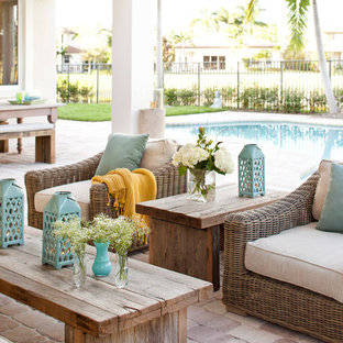 Design ideas for a large transitional backyard patio in Miami with brick pavers and a roof extension.