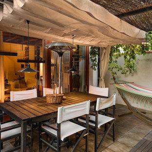 Modelo de patio tropical, pequeño, en patio, con suelo de baldosas, toldo y jardín vertical