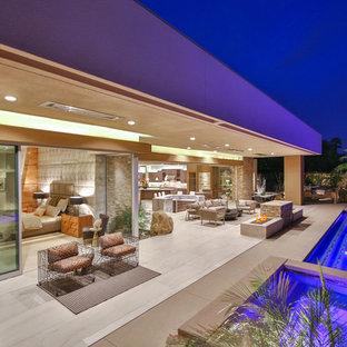 Foto di un ampio patio o portico design dietro casa con un focolare, piastrelle e un tetto a sbalzo