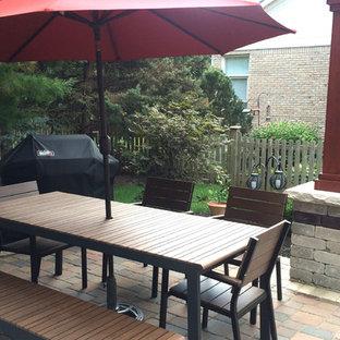 Foto di un patio o portico etnico di medie dimensioni e dietro casa con un focolare, pavimentazioni in mattoni e nessuna copertura