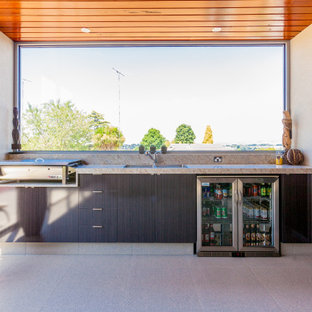 Mid-sized contemporary backyard patio in Melbourne with an outdoor kitchen, tile and a roof extension.