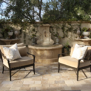 Large tuscan courtyard concrete paver patio fountain photo in Orange County