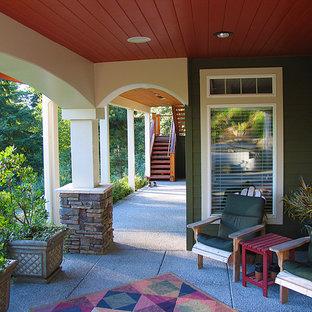 Foto di un grande patio o portico american style dietro casa con un tetto a sbalzo, un giardino in vaso e lastre di cemento