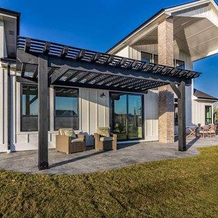 Inspiration för lantliga uteplatser på baksidan av huset, med utekök, stämplad betong och en pergola