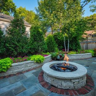 Esempio di un patio o portico tradizionale di medie dimensioni e dietro casa con un focolare, pavimentazioni in pietra naturale e nessuna copertura