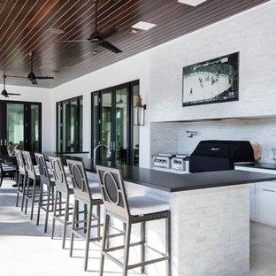 Diseño de patio clásico, en patio trasero y anexo de casas, con cocina exterior y suelo de baldosas