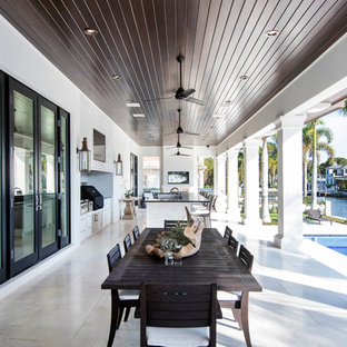 This is an example of a traditional back patio in Tampa with an outdoor kitchen, tiled flooring and a roof extension.