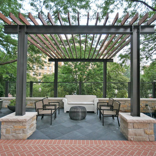 This is an example of a large contemporary courtyard patio in Chicago with natural stone pavers and a pergola.