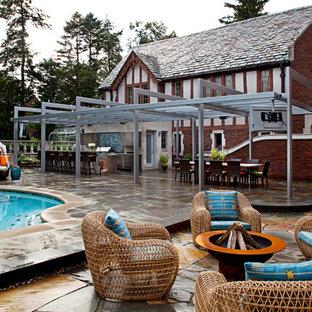Idee per un grande patio o portico boho chic dietro casa con un focolare, una pergola e pavimentazioni in pietra naturale