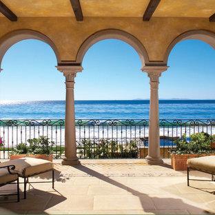 Exemple d'une terrasse méditerranéenne avec une extension de toiture.