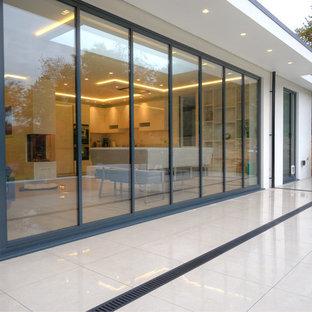 Foto di un grande patio o portico minimal dietro casa con piastrelle