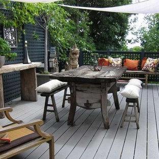 Esempio di un patio o portico etnico di medie dimensioni con pedane e un parasole