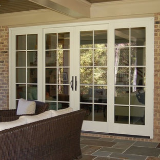 Immagine di un patio o portico chic di medie dimensioni e dietro casa con un focolare, graniglia di granito e un tetto a sbalzo