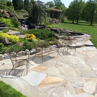 Patio fountain - mid-sized traditional backyard stone patio fountain idea in Wilmington with no cover