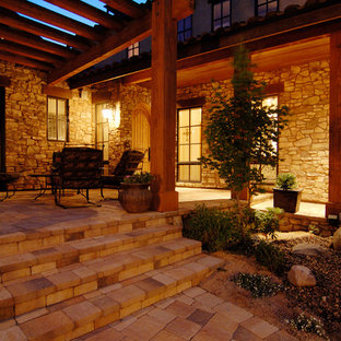 Inspiration for a large traditional courtyard patio in Other with a container garden, natural stone pavers and a roof extension.