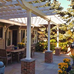 Immagine di un patio o portico stile americano di medie dimensioni e dietro casa con pavimentazioni in pietra naturale e una pergola