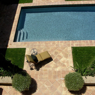 Photo of a large mediterranean backyard patio in Orange County with a water feature, tile and no cover.