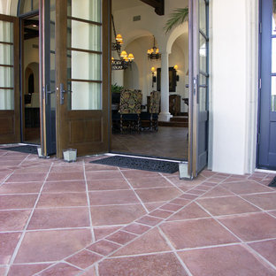 Photo of a large mediterranean backyard patio in Orange County with tile and no cover.