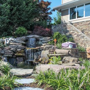 Foto di un grande patio o portico shabby-chic style dietro casa con fontane, pavimentazioni in mattoni e un gazebo o capanno
