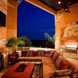 Esempio di un patio o portico mediterraneo con pavimentazioni in pietra naturale e un tetto a sbalzo