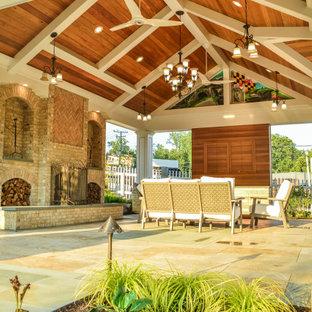 Esempio di un grande patio o portico american style dietro casa con un caminetto, pavimentazioni in pietra naturale e un gazebo o capanno