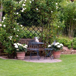 Immagine di un piccolo patio o portico country nel cortile laterale con pavimentazioni in pietra naturale e nessuna copertura