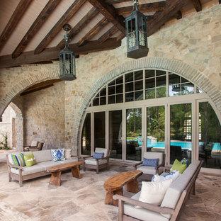 На фото: класса люкс огромные дворики на заднем дворе в средиземноморском стиле с покрытием из каменной брусчатки и навесом