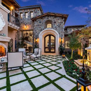 Immagine di un ampio patio o portico stile shabby in cortile con un focolare, pavimentazioni in cemento e nessuna copertura