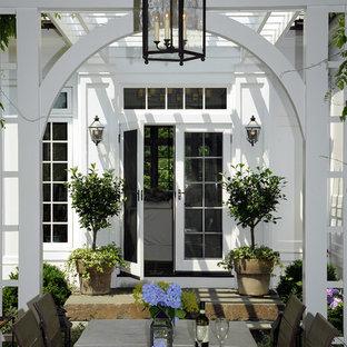 Idéer för en stor klassisk uteplats på baksidan av huset, med takförlängning och en öppen spis