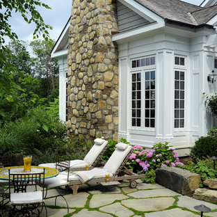 Example of a large classic backyard stone patio design in New York with a pergola
