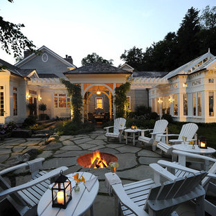 Inspiration for a large timeless backyard stone patio remodel in New York with a fire pit and no cover