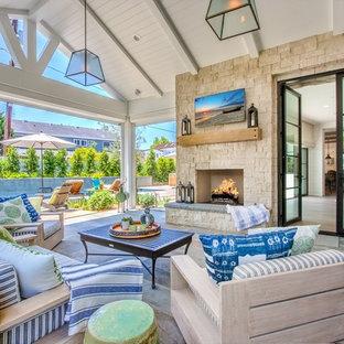 Пример оригинального дизайна интерьера: дворик в стиле кантри с покрытием из каменной брусчатки, навесом и уличным камином
