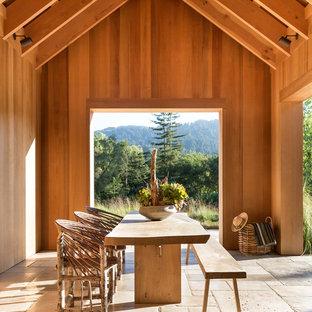 Esempio di un ampio patio o portico country con un tetto a sbalzo