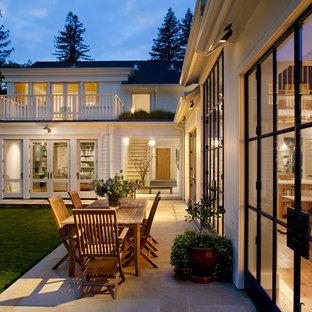 Foto di un patio o portico country dietro casa con piastrelle e nessuna copertura