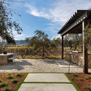 Ispirazione per un ampio patio o portico country dietro casa con ghiaia e un gazebo o capanno