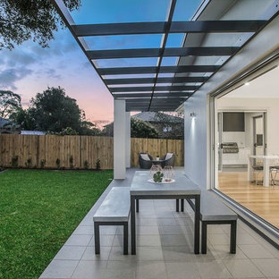 Contemporary patio in Sydney with concrete pavers and a pergola.