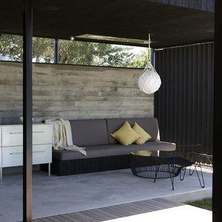 Inspiration för en funkis uteplats, med betongplatta och takförlängning